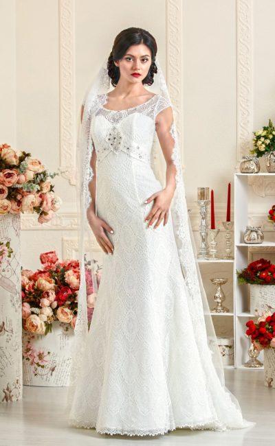 Лаконичное свадебное платье необычным оформлением талии, покрытое кружевом.