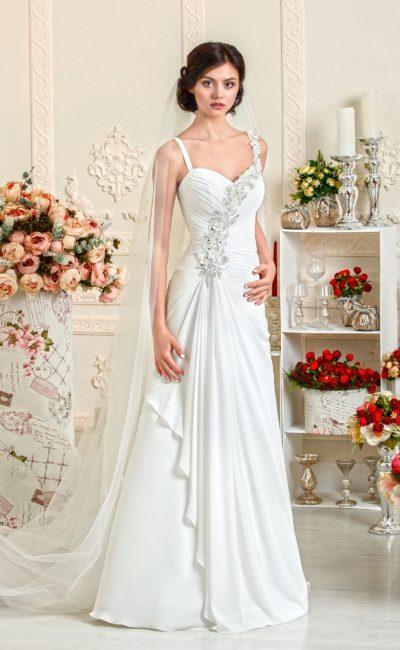 Прямое свадебное платье, декорированное драпировками и сверкающей вышивкой.
