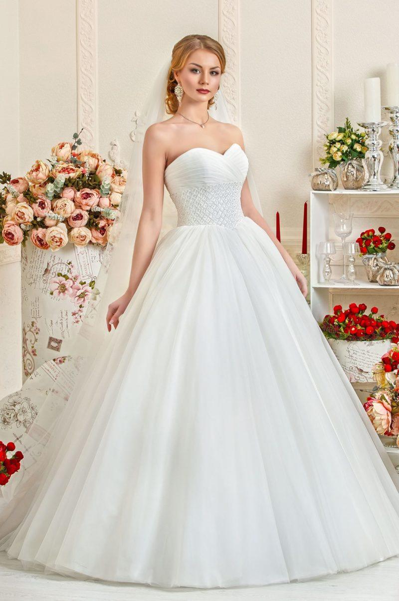 Пышное свадебное платье с открытым корсетом, украшенным вышивкой по линии талии.