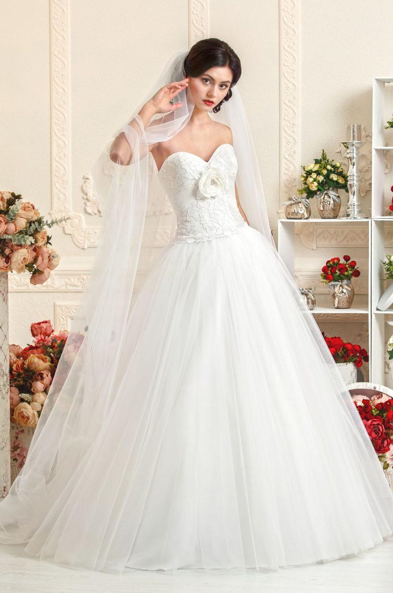 Пышное свадебное платье с отделкой крупным кружевом и объемным бутоном на лифе.