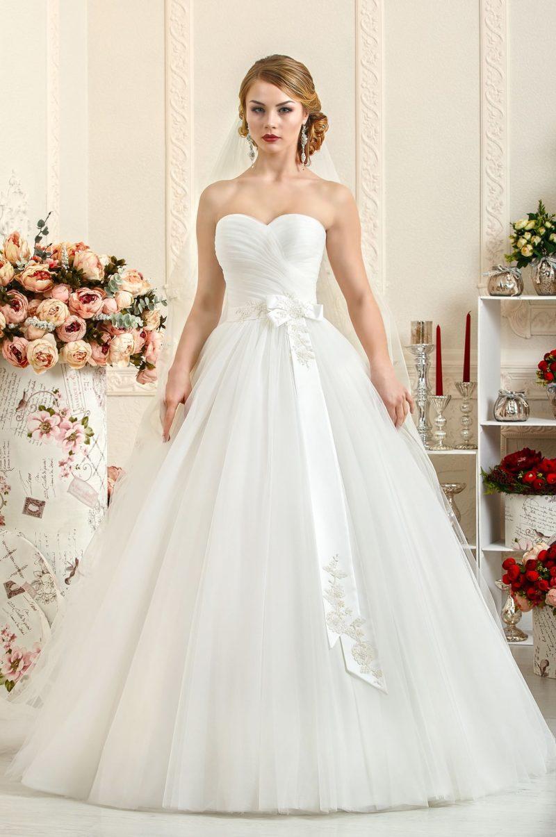 Женственное свадебное платье с открытым корсетом, дополненным атласным поясом.