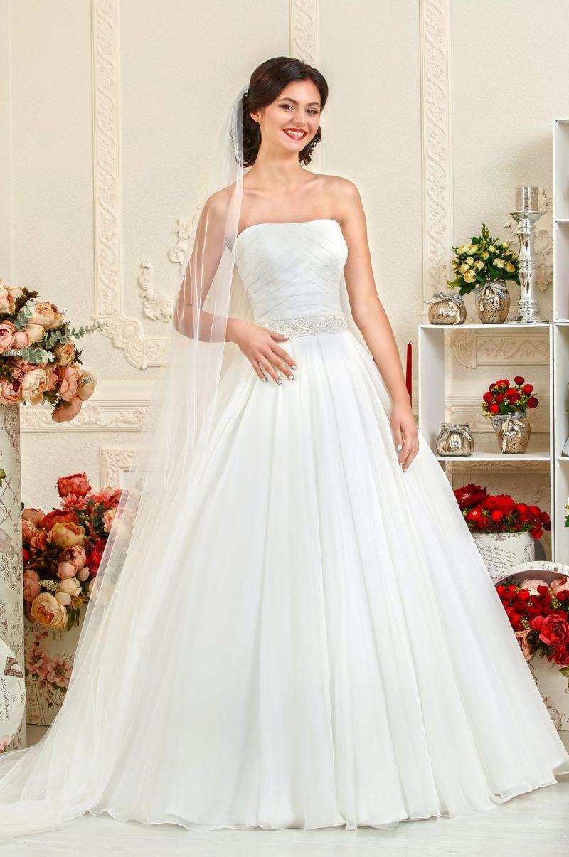 Традиционное свадебное платье А-силуэта с открытым лифом, покрытым драпировками.