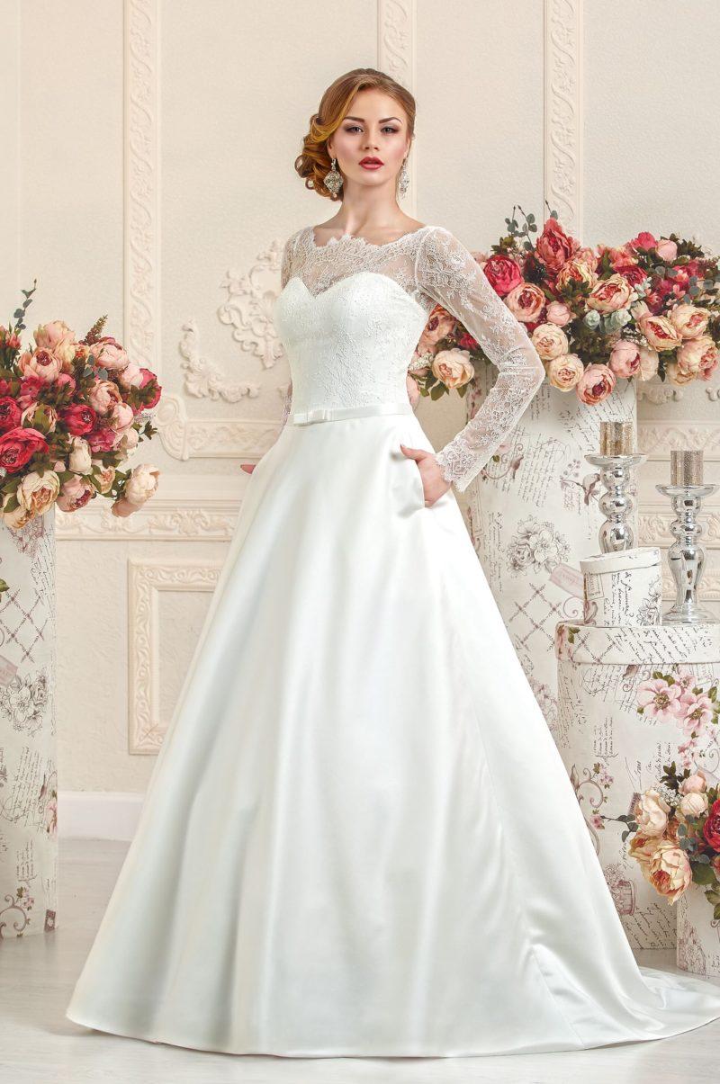 Свадебное платье с атласной юбкой со скрытыми карманами и лифом с длинными кружевными рукавами.