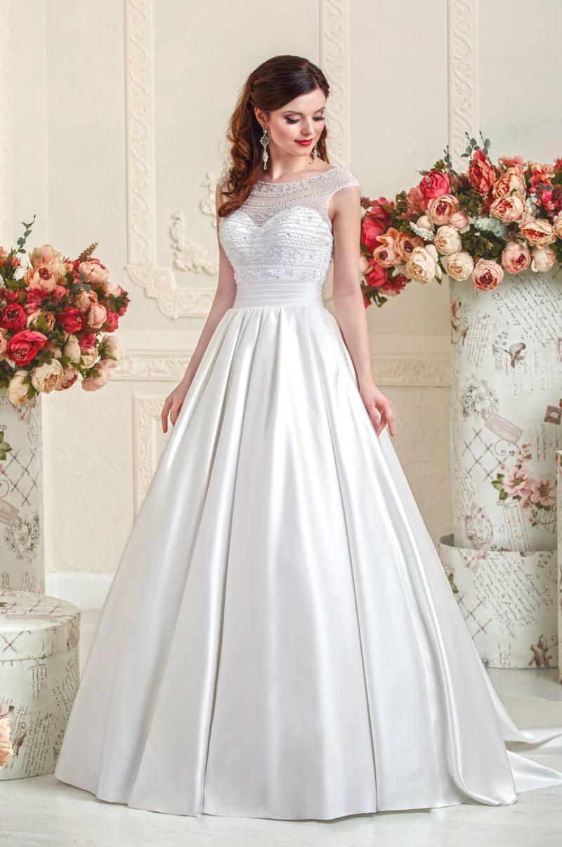 Изысканное атласное свадебное платье с верхом, покрытым тонкой тканью с вышивкой.