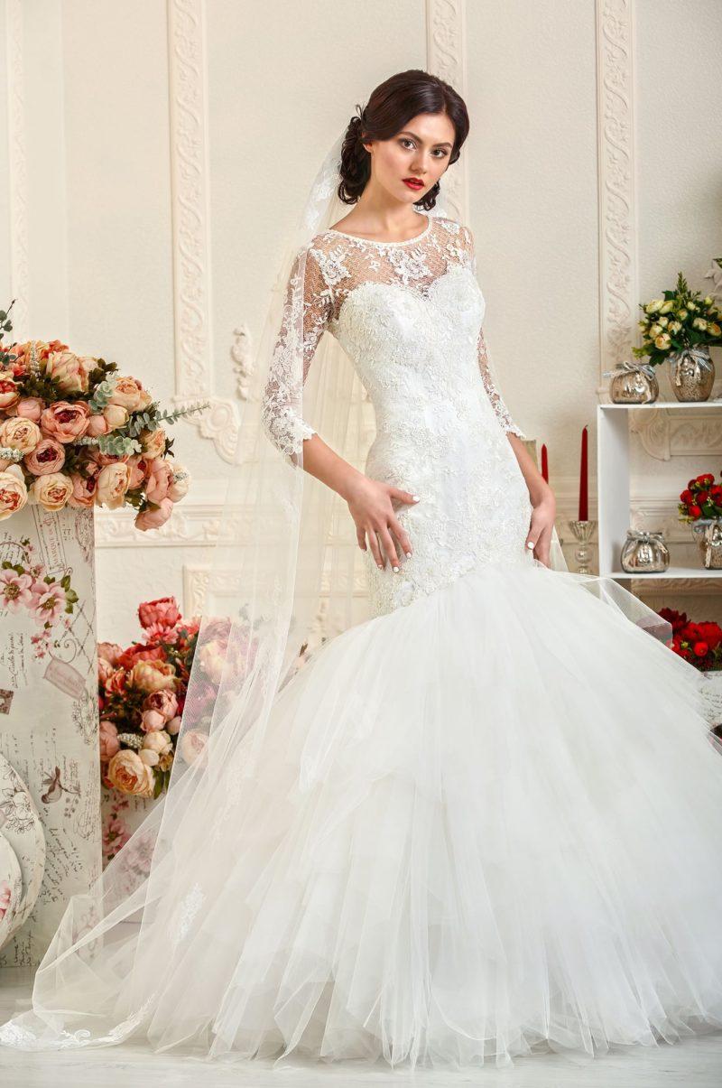 Закрытое свадебное платье с подчеркнуто пышной юбкой «рыбка» и кружевными рукавами.