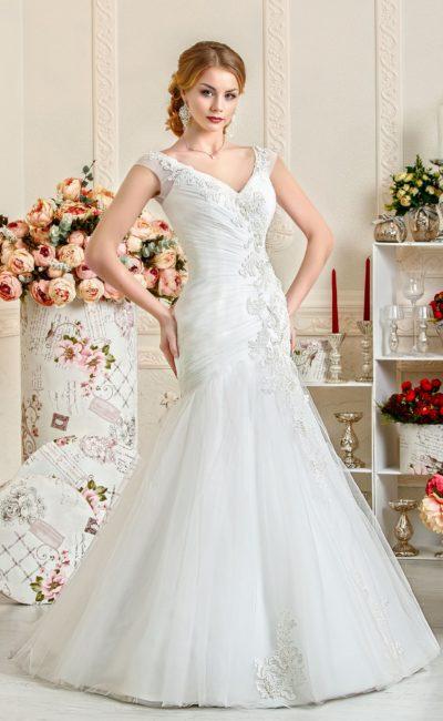 Облегающее свадебное платье с декором из драпировок и аппликаций, дополненное широкими бретелями.