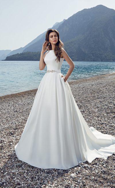 Изысканное свадебное платье из атласной ткани с бисерной вышивкой на талии и шлейфом сзади.