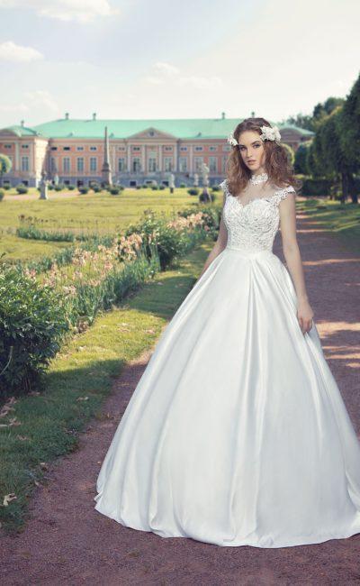 Роскошное свадебное платье с атласной юбкой и облегающим верхом, украшенным тонкой тканью.
