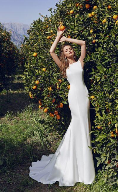 Утонченное свадебное платье из атласной ткани, с вырезом под горла и облегающим силуэтом.