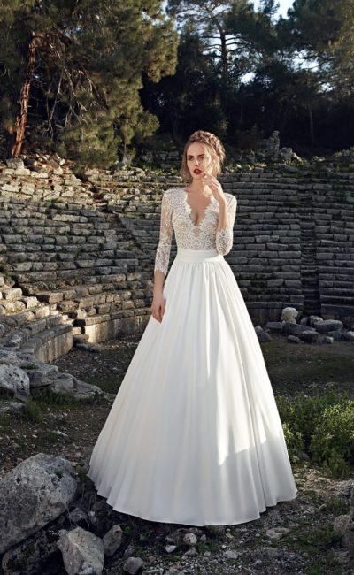 Свадебное платье с пышной фактурной юбкой и глубоким декольте с кружевным декором верха.