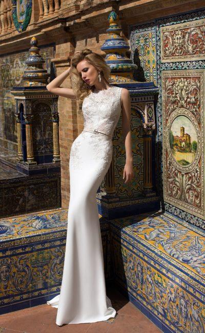 Облегающее свадебное платье с фактурным декором закрытого лифа и узким поясом на талии.