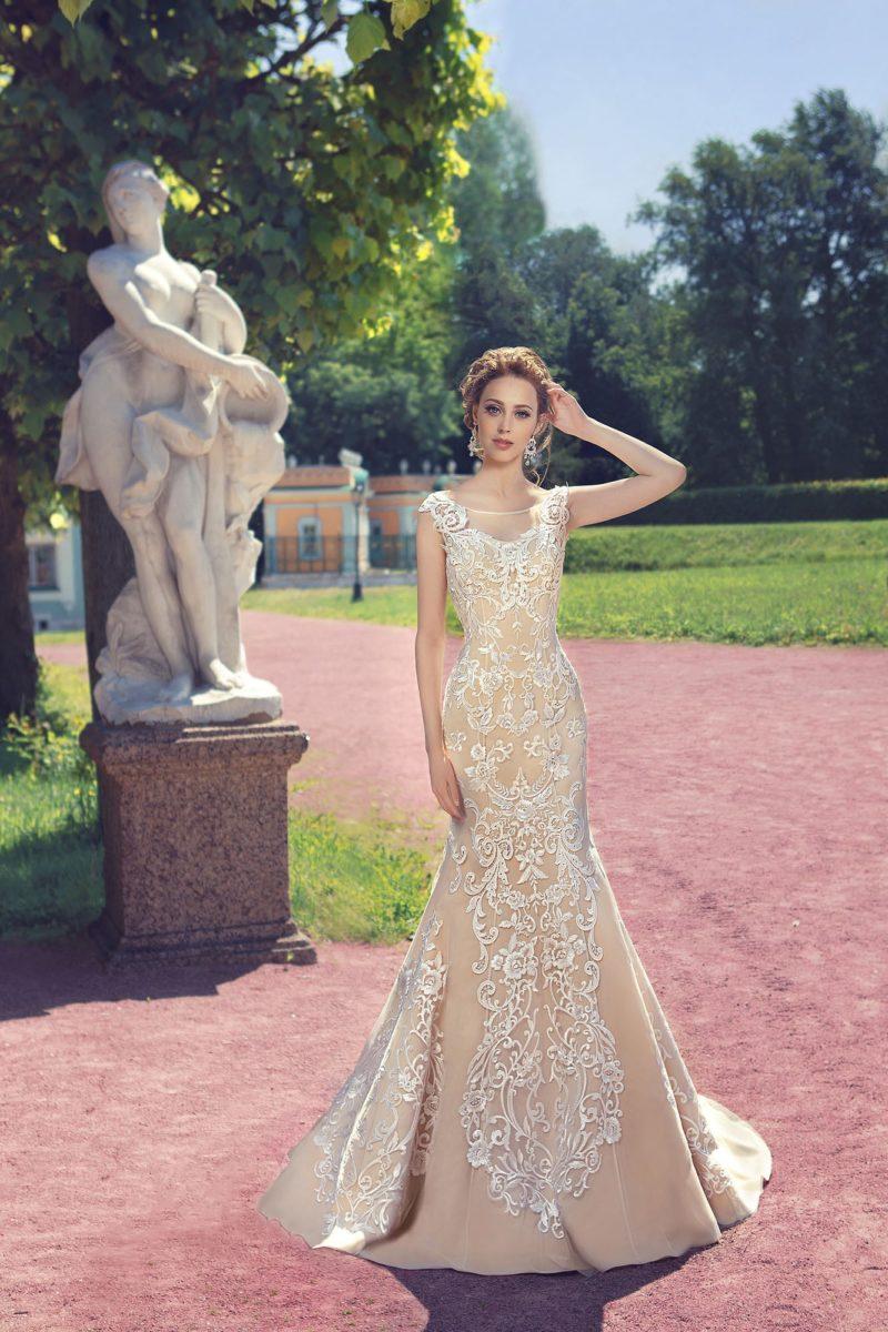 Шикарное свадебное платье бежевого цвета с отделкой белыми аппликациями и открытым верхом.