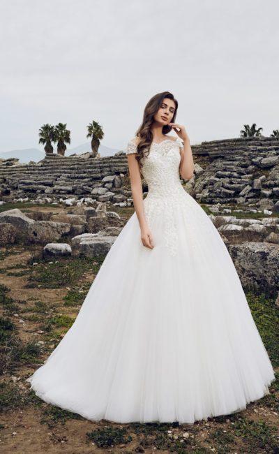 Свадебное платье с многослойной юбкой со шлейфом, дополненное портретным декольте.