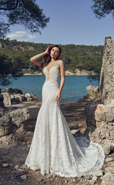 Облегающее свадебное платье с фигурным глубоким декольте, оформленное кружевной тканью.