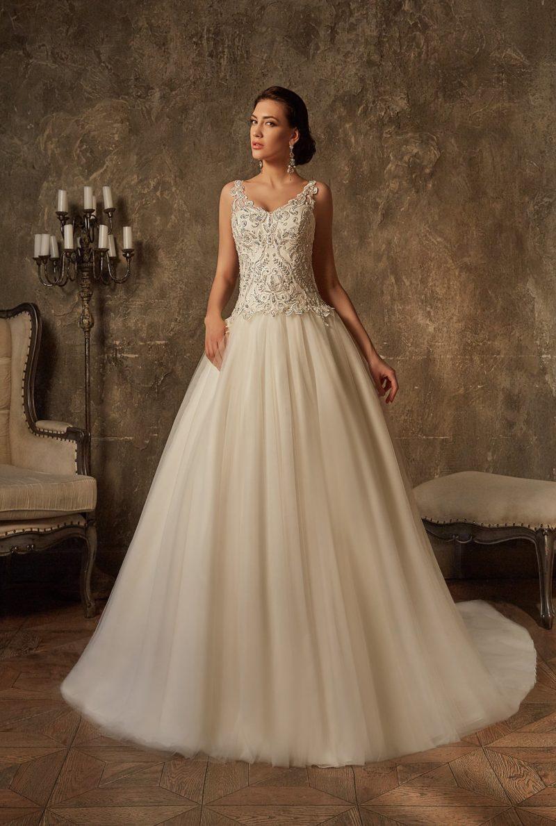 Нежное свадебное платье с объемной юбкой и лифом, покрытым бисерной вышивкой.