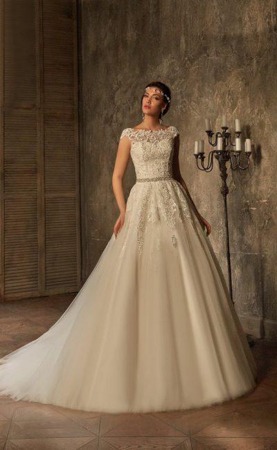 Свадебное платье с закрытым кружевным лифом, узким поясом и объемной юбкой со шлейфом.