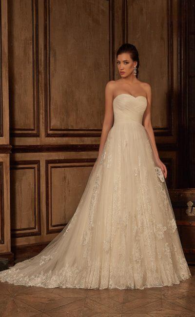 Открытое свадебное платье с драпировками на корсете и пышной юбкой, декорированной кружевом.