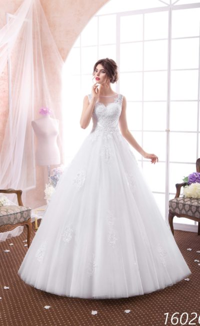 Пышное свадебное платье с тонкой вставкой над лифом и лаконичным многослойным низом.
