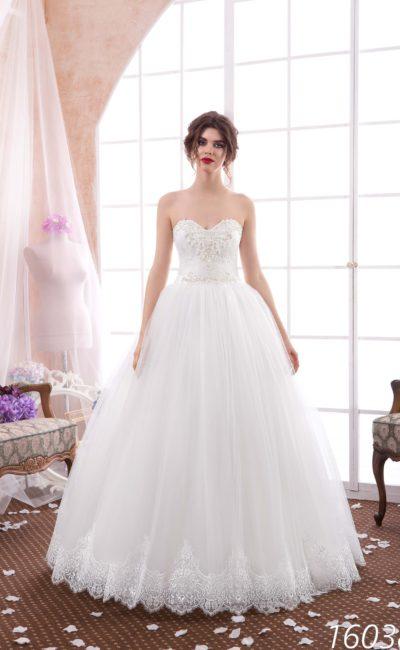 Нежное свадебное платье пышного кроя с кружевом по низу подола и изящным открытым верхом.