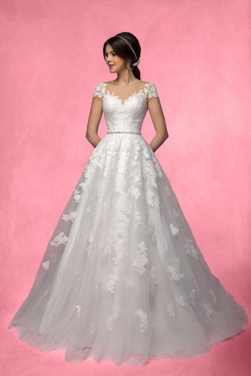 Свадебное платье с романтичной многослойной юбкой, украшенной крупными кружевными аппликациями.
