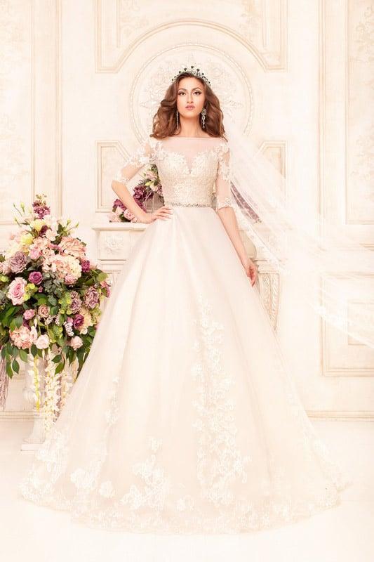 Нежное свадебное платье с кружевной отделкой, длинными рукавами и узким сияющим поясом.