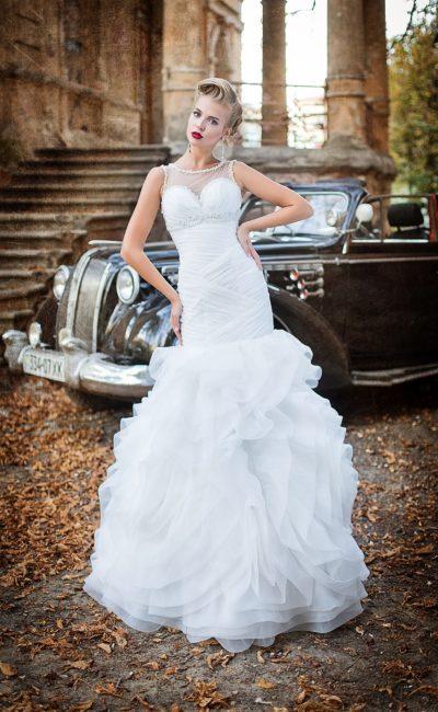 Притягательное свадебное платье с закрытым лифом и объемной юбкой, покрытой оборками.