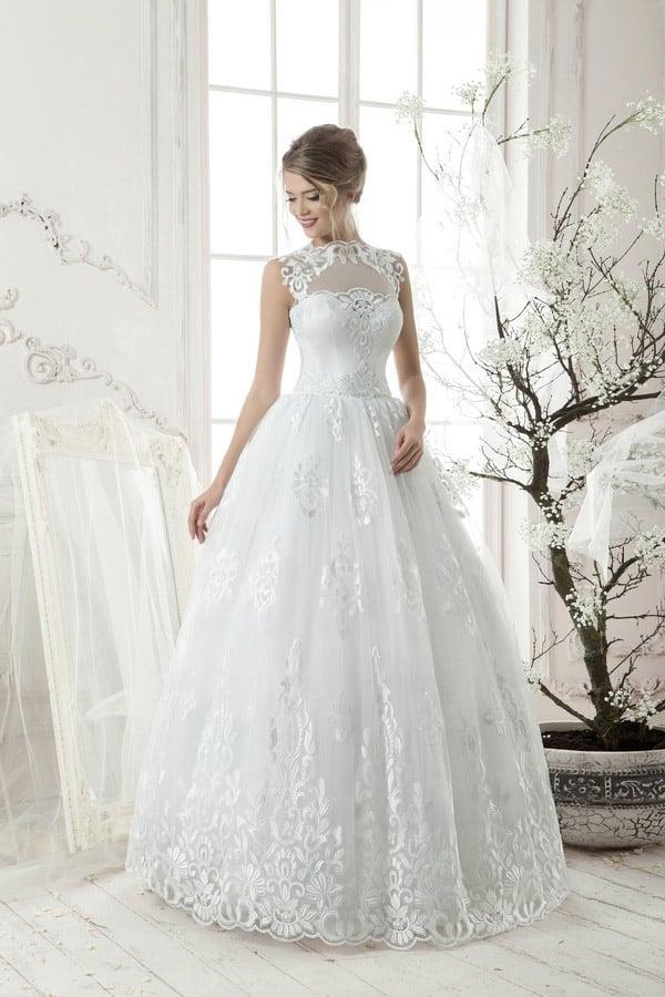 Закрытое свадебное платье пышного кроя, выразительно декорированное кружевными аппликациями.
