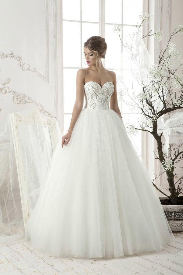Пышное свадебное платье с открытым корсетом, украшенным крупным бисерным узором вышивки.