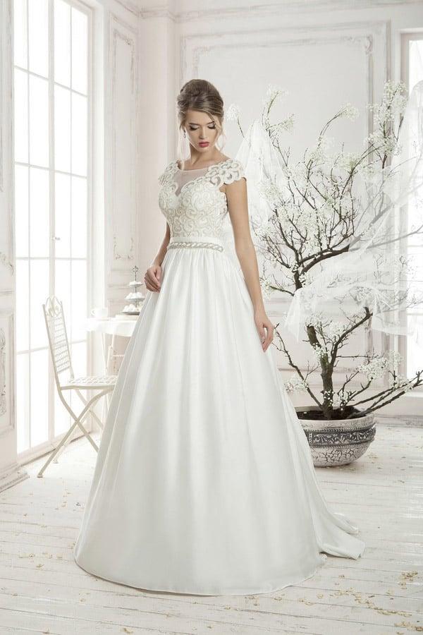 Стильное свадебное платье с атласной юбкой и закрытым кружевным верхом с вырезом под горло.
