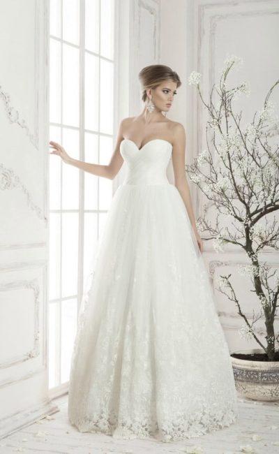 Соблазнительное открытое свадебное платье с драпировками по верху и юбкой с кружевным декором.