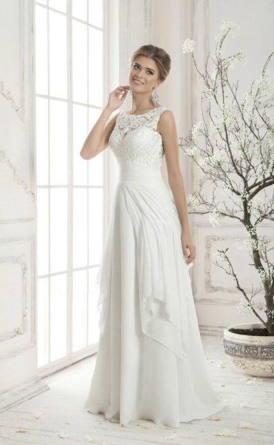 Закрытое свадебное платье «трапеция» с кружевным верхом и юбкой, покрытой оборками.