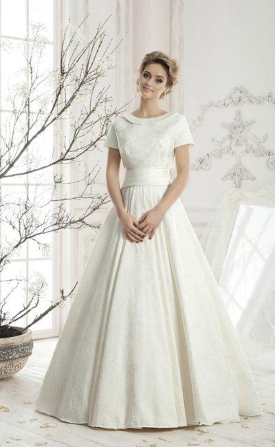 Фактурное свадебное платье «трапеция» с вырезом на спинке и атласным болеро с коротким рукавом.