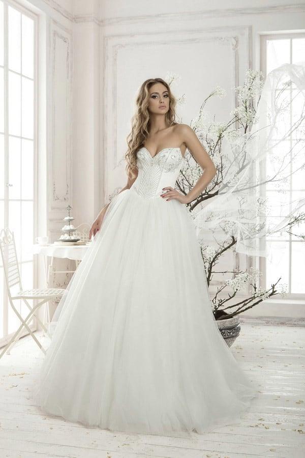 Романтичное свадебное платье пышного кроя с роскошным открытым корсетом, подчеркивающим декольте.
