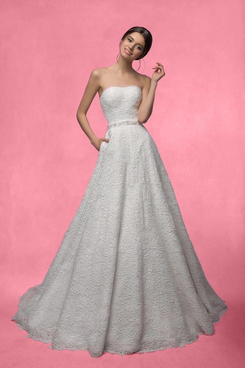 Фактурное свадебное платье с открытым корсетом и скрытыми карманами в юбке А-силуэта.