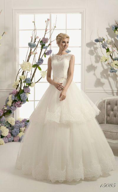 Закрытое свадебное платье пышного кроя с кружевной многоярусной юбкой и вышитым поясом.