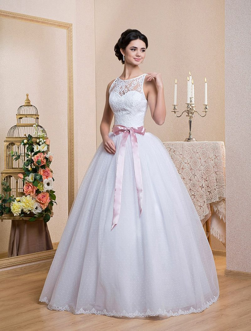 Пышное свадебное платье с округлым вырезом и широким атласным поясом розового цвета.