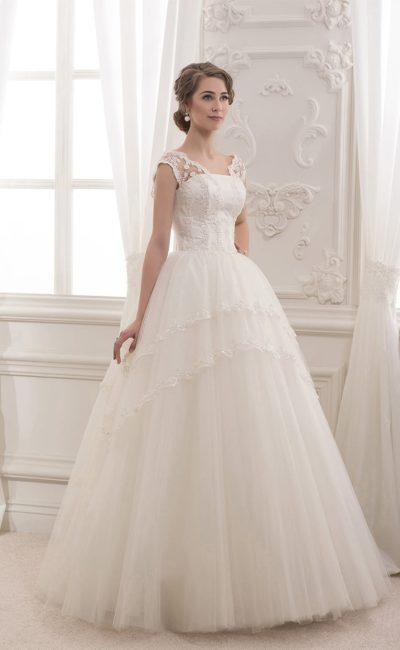 Романтичное свадебное платье с широкими бретелями и многоуровневым подолом.