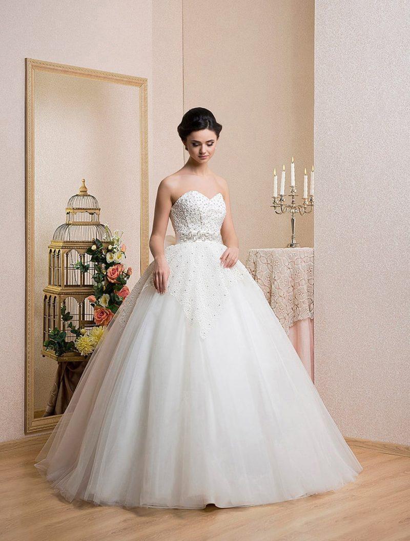 Стильное свадебное платье с открытым лифом в форме сердца, украшенным бисерной вышивкой.