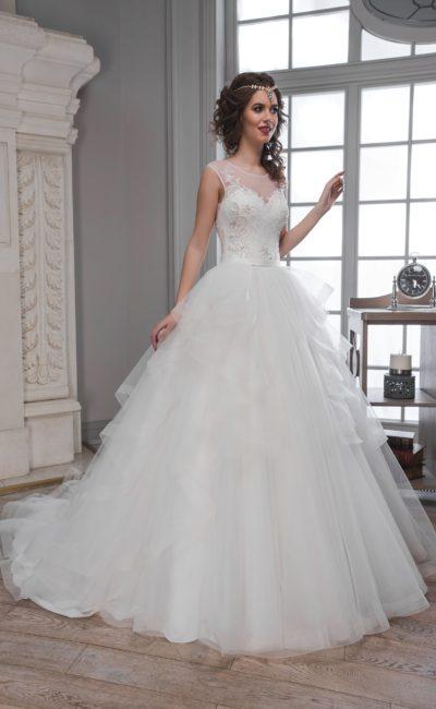 Свадебное платье с пышными полупрозрачными оборками на юбке и элегантным верхом.