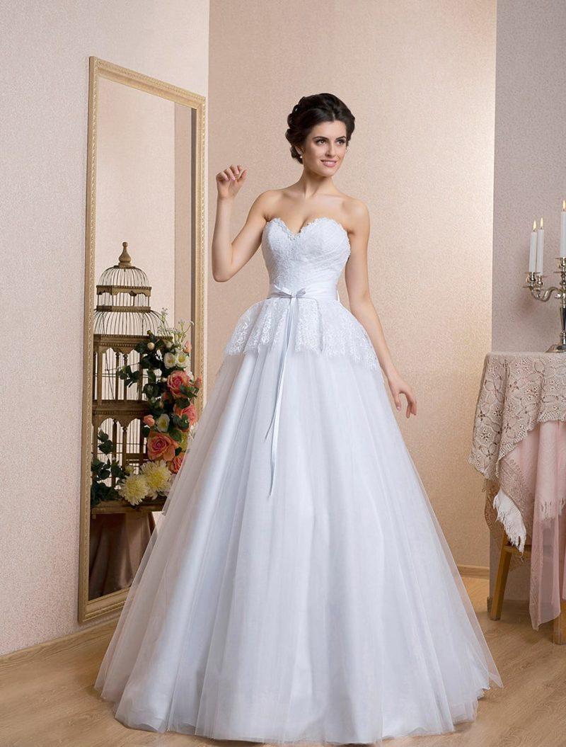 Свадебное платье с глубоким декольте в форме сердца и кружевной отделкой баски.