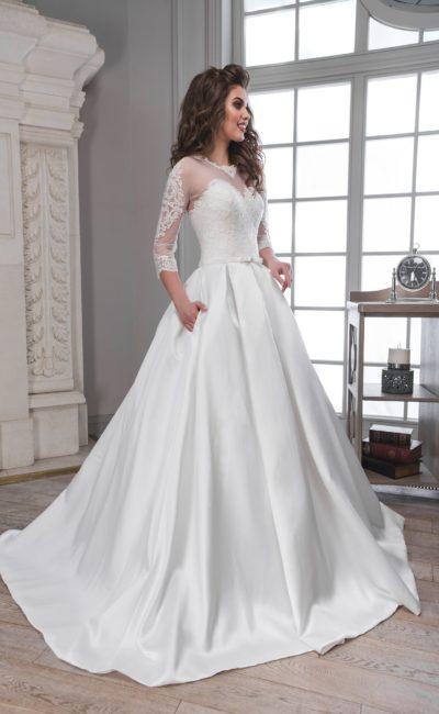 Атласное свадебное платье со скрытыми карманами и длинными полупрозрачными рукавами.