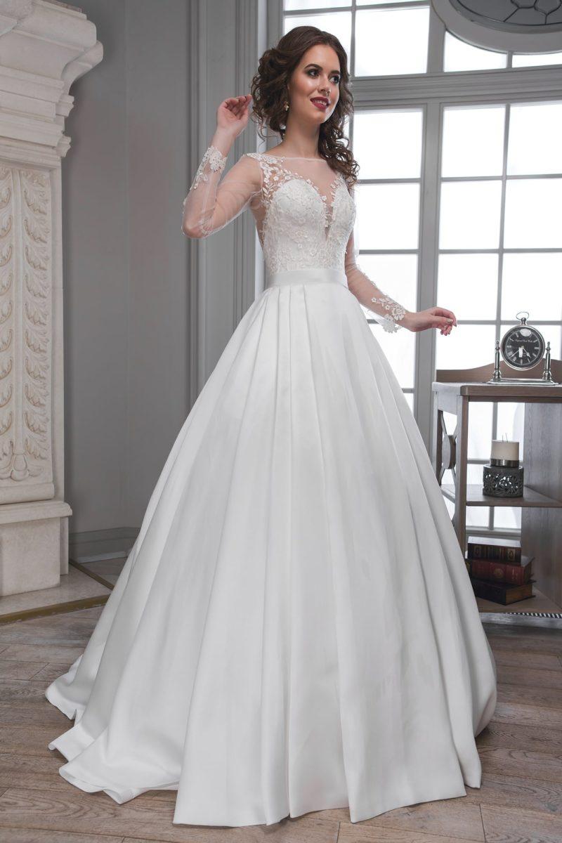 Выразительное свадебное платье пышного кроя с полупрозрачной отделкой верха и длинным рукавом.