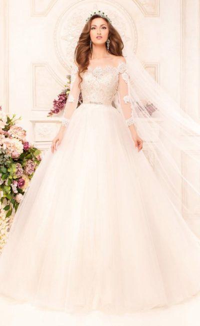 Свадебное платье оттенка айвори с кружевными аппликациями по корсету и длинными рукавами.