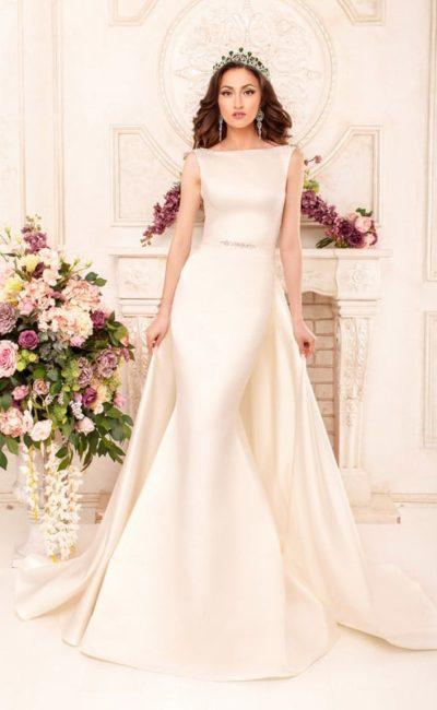 Впечатляющее свадебное платье из атласной ткани, с округлым вырезом и накидкой сзади.