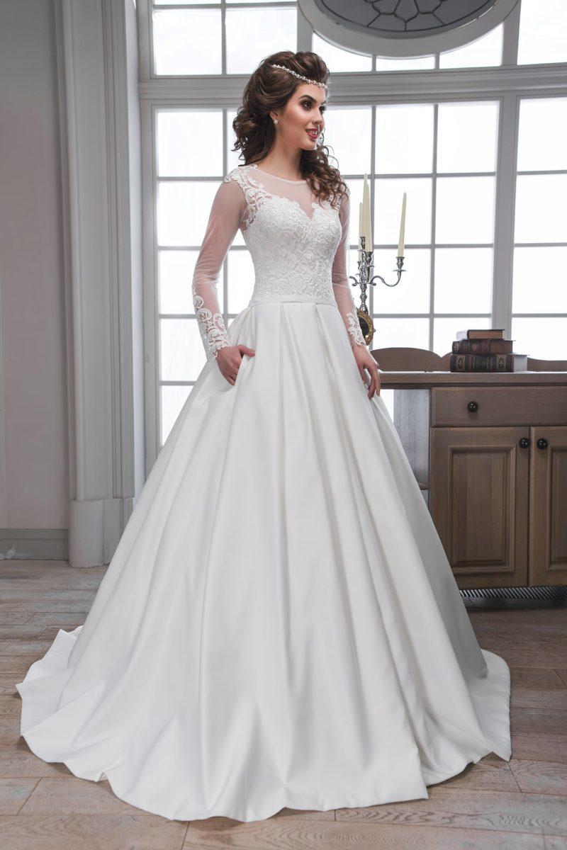 Классическое свадебное платье с атласной пышной юбкой и длинными кружевными рукавами.