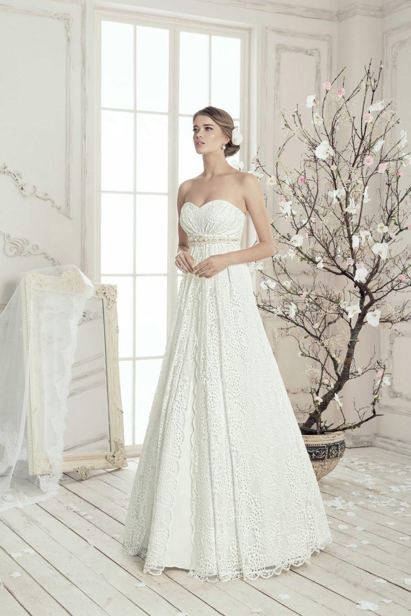 Деликатное свадебное платье с кружевной отделкой, завышенной талией и поясом с вышивкой.