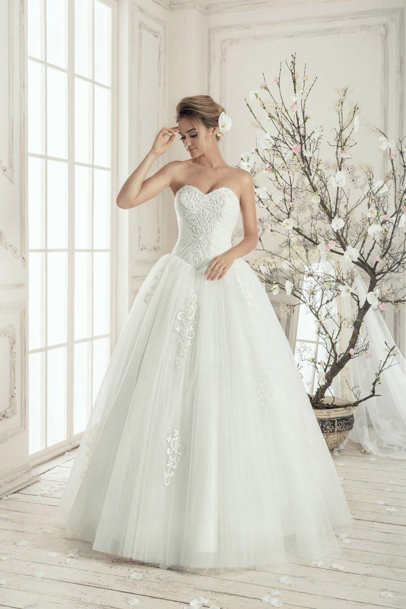 Пышное свадебное платье с роскошным корсетом, украшенным драпировками и аппликациями.