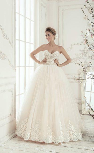 Пышное свадебное платье цвета слоновой кости с отделкой кружевом с крупным рисунком по лифу.