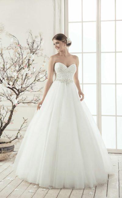 Свадебное платье с открытым лифом традиционного кроя и пышной многослойной юбкой.