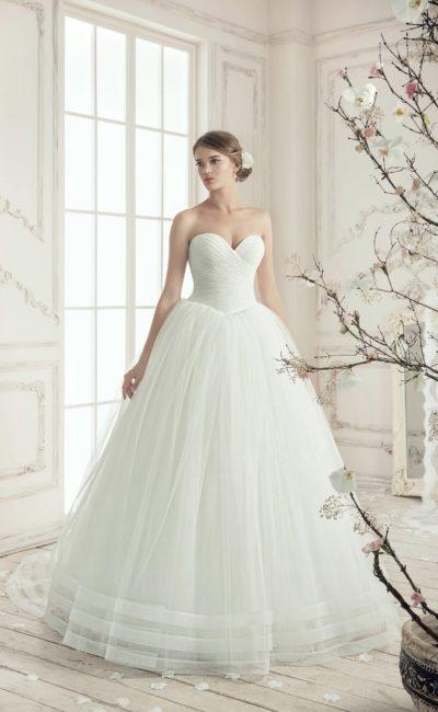 Пышное свадебное платье с изящными драпировками на корсете и подолом, украшенным тесьмой.